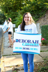 Girl holding yard sign that says Deborah Gonzalez
